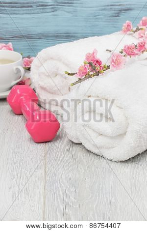 Healthy living concept- hand weight, towels and tea