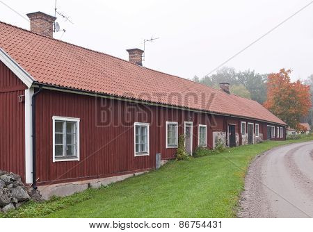 Wooden red building along a gravel road.