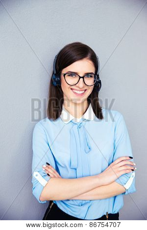 Smiling female operator with phone headset and arsm folded over gray background. Wearing in blue shirt and glasses. Looking at camera