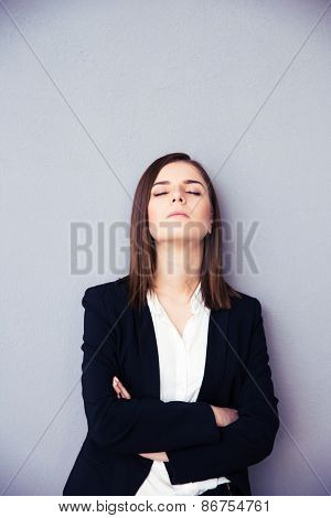 Tired businesswoman with arms folded sleeping over gray background