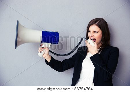 Beautiful young businesswoman with megaphone over gray background. Looking away.