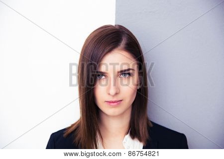 Portrait of a cute young businesswoman standing over half white and half gray background. Looking at camera