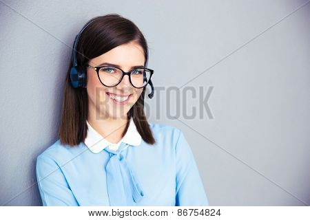Smiling female operator with phone headset over gray background. Wearing in blue shirt and glasses. Looking at camera