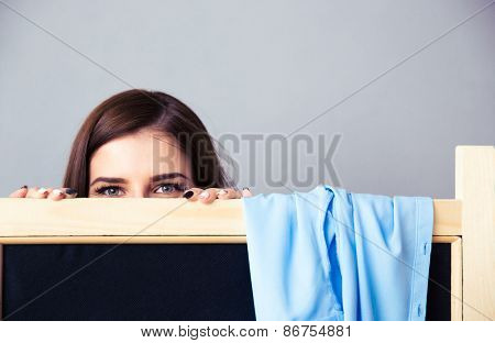 Young woman looking out from the locker room over gray background