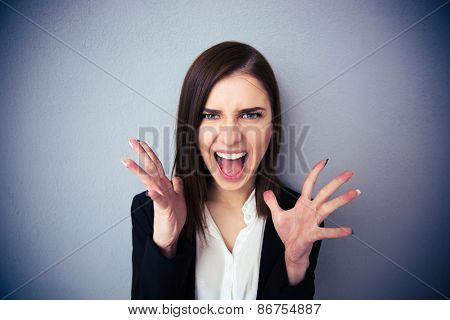 Angry woman screaming over gray background. Looking at camera