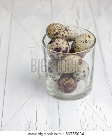 Many Spotted Quail Eggs In The Glass On The Wooden Table