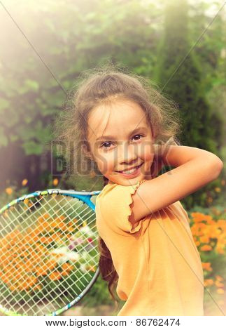 Toned portrait of pretty little girl playing tennis outdoors