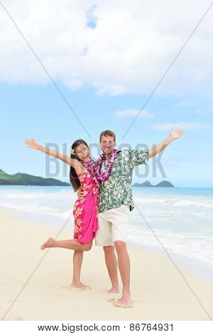 Happy Hawaii vacation couple having fun on beach holidays in Hawaii standing on perfect white sand with arms up in joy and happiness. People ready for summer vacations showing freedom and success.