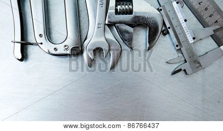 Many tools on the scratched metal background.