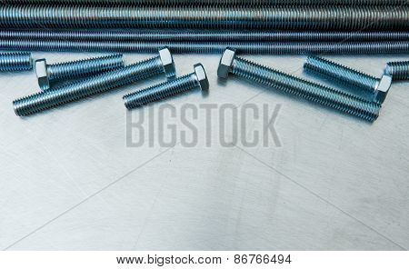 Metal hairpins and bolts on the scratched metal background.