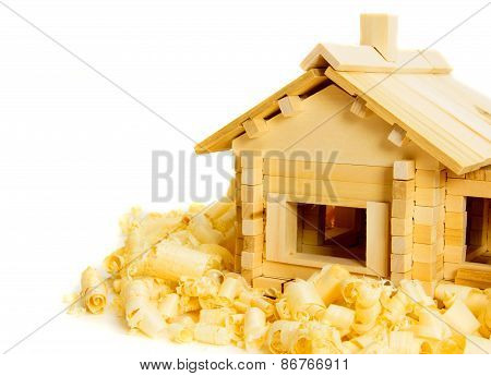 House construction. Joiner's works. The wooden house and shaving on white background.