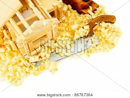 House construction. Joiner's works. The small wooden house, saw, plane and shaving on white backgrou