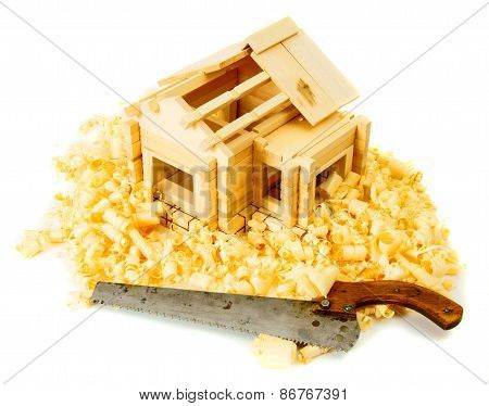 House construction. Joiner's works. The small wooden house, saw and shaving on white background.