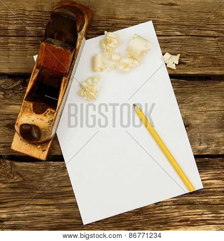 Paper with pencil and the vintage working tool on wooden background.