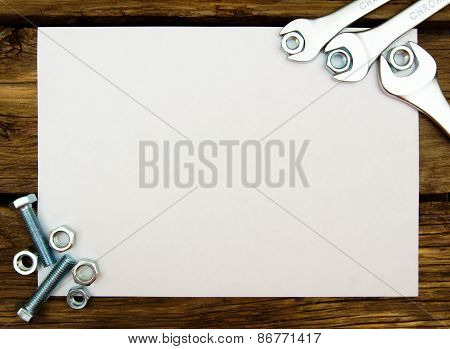 The Sheet of paper and fixing elements, wrenches on wooden background.