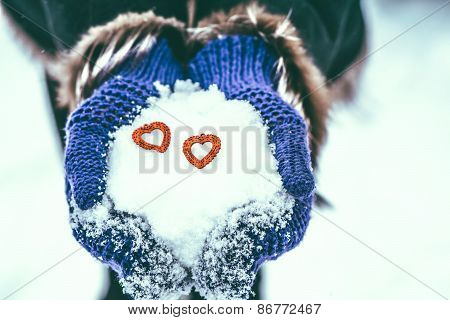 Red Wooden Hearst In The Hands With Snow