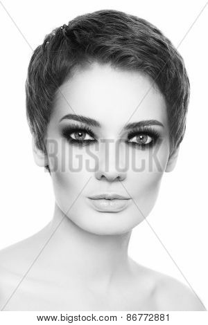 Black and white portrait of young beautiful woman with stylish short haircut and smoky eyes over white background