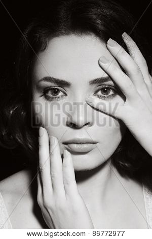 Black and white portrait of woman touching her face, vintage style
