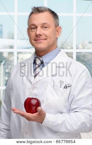 Dentist holding red apple
