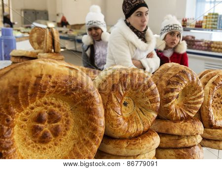 BUKHARA, UZBEKISTAN - MARCH 14, 2015: City grocery market. Women sell traditional Uzbek bread.