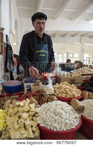 BUKHARA, UZBEKISTAN - MARCH 14, 2015: City grocery market. Man sells traditional Uzbek sweets.