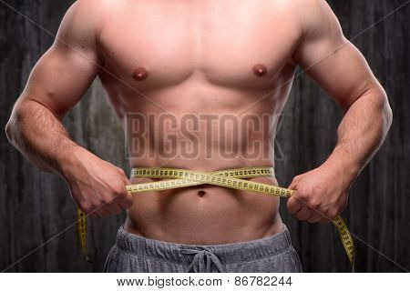 Close up of well formed man measuring his waist