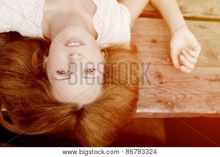 Girl lying on the wooden floor in the sunlight. Beautiful young woman on sunset light. Hipster, youth lifestyle Backlit and toned. sunshine glow sun, sunbeams Enjoying nature outdoor. Freedom concept