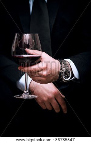 adult elegant man hold glass of red wine, close up, indoor shot, selective focus