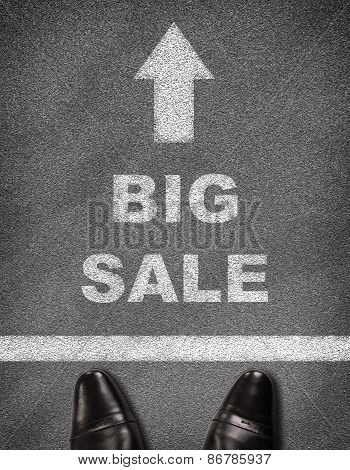 Shoes standing on asphalt road with arrow, line and text BIG SALE