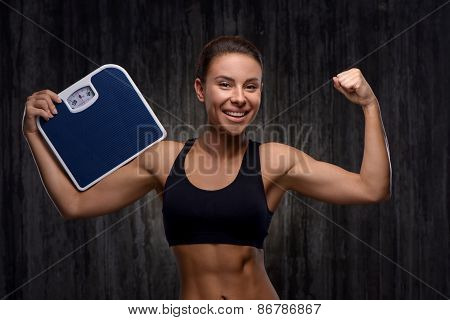 Smiling mixed race sporty woman holding weighs