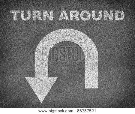 Asphalt road texture with U-turn sign and text turn around