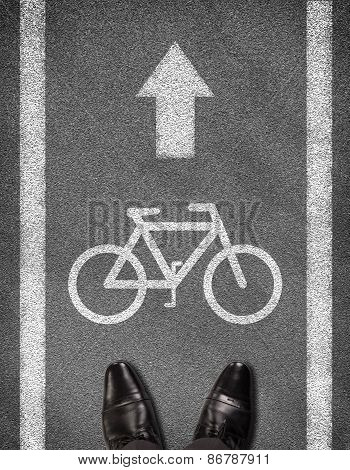 Shoes standing on asphalt road with two line and bicycle sign