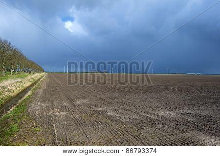 Plowed field under a rain shower in spring