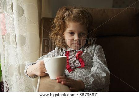 Thoughtful Little Girl With A Mug