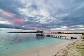 stock photo of tourist-spot  - Romantic cloudy sky coral spotted sea and wooden jetty in tourist resort in the remote Togian  - JPG