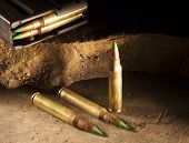 foto of cartridge  - Three rifle cartridges with green tips and a loaded magazine - JPG