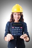 stock photo of overspending  - Female builder with calculator on white - JPG