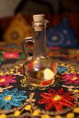 stock photo of vinegar  - Decanter of flavored vinegar on the embroidered tablecloth in an asian restaurant - JPG