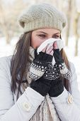 foto of blowing nose  - Young Woman in Winter Clothing Blowing Nose with tissue paper outdoor - JPG