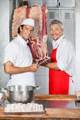 stock photo of slaughterhouse  - Portrait of happy butchers working together in butchery - JPG
