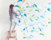 image of wall painting  - 8 years old girl painting the wall at home - JPG