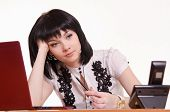 stock photo of polite girl  - Cute little girl sitting at a table in the call center with laptop in white blouse propped his head on his hand - JPG