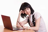 stock photo of polite girl  - Cute little girl sitting at a table in the call center with laptop in white blouse - JPG
