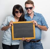 stock photo of multicultural  - A portrait of Happy Young Multiculture Couple posing with chalk board - JPG