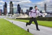 image of running-late  - Running businessman in a hurry and modern city in background - JPG