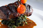 picture of chateaubriand  - Chateaubriand steak served with grilled tomatoes on top of the cooked spinach - JPG