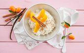 picture of kumquat  - Bowl of rice pudding with peaches and kumquat - JPG