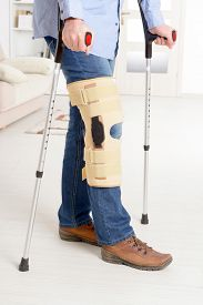 picture of stability  - Man with leg in knee cages and crutches for stabilization and support  - JPG
