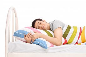 picture of sweet dreams  - Young joyful man sleeping in a comfortable bed and dreaming sweet dreams covered with a blanket and hugging the pillow isolated on white background - JPG