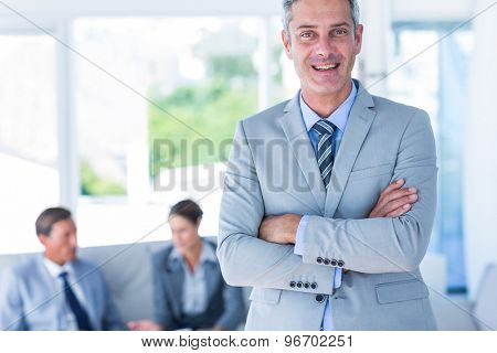 Businessman looking at camera with his colleagues behind him in office